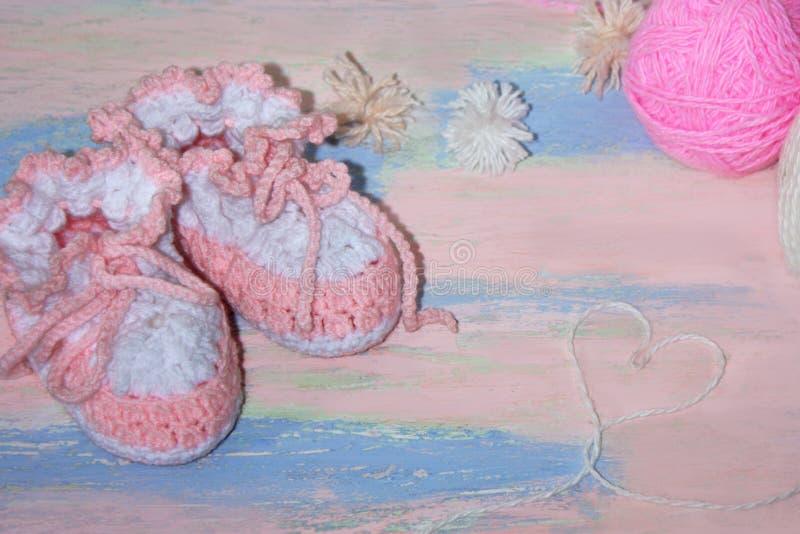 Το άσπρος-ροζ έπλεξε τις λείες παπουτσιών μωρών σε έναν ρόδινος-μπλε ξύλινο πίνακα με τις σφαίρες του νήματος και μιας καρδιάς τω στοκ εικόνα με δικαίωμα ελεύθερης χρήσης