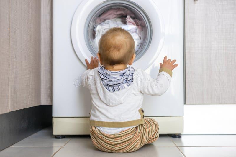 Το άσπρο πλυντήριο κρατά πολυάσχολο το μικρό αγοράκι στοκ φωτογραφία με δικαίωμα ελεύθερης χρήσης