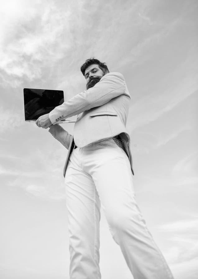Το άτομο εκαλλώπισε καλά το γενειοφόρο hipster κρατά το υπόβαθρο μπλε ουρανού lap-top Τύπων επίσημος διευθυντής τεχνολογίας κοστο στοκ εικόνα
