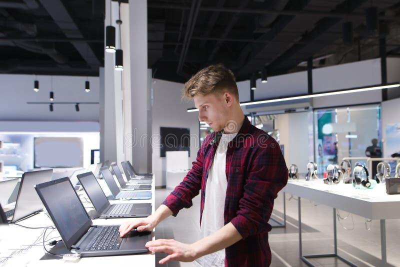 Το άτομο εξετάζει τα lap-top στο τμήμα υπολογιστών στο κατάστημα τεχνολογίας Αγοράστε ένα lap-top στοκ φωτογραφία