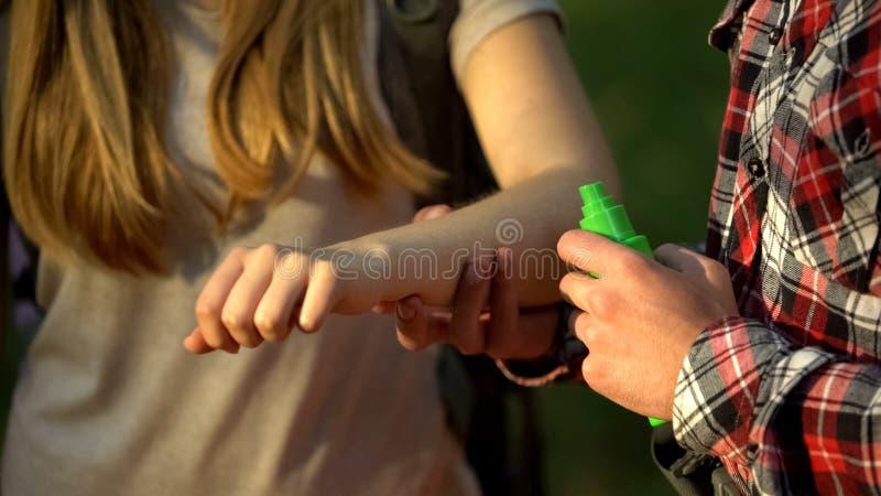 Το άτομο που εφαρμόζει τη δροσίζοντας κρέμα στο γυναικείο βραχίονα μετά από τα κουνούπια δαγκώνει, απωθητική ουσία εντόμων στοκ φωτογραφίες