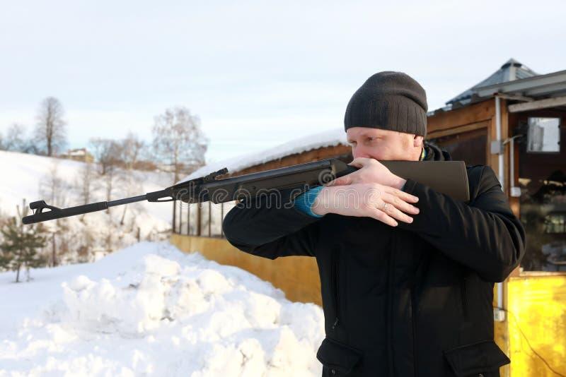 Το άτομο πυροβολεί το τουφέκι αέρα στοκ εικόνα