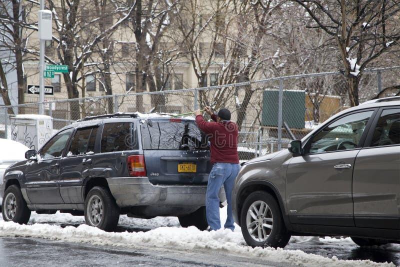 Το άτομο Bronx καθαρίζει το όχημά του μετά από τη θύελλα χιονιού στοκ εικόνες