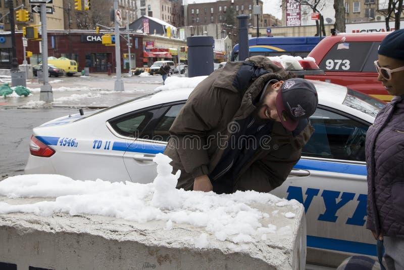 Το άτομο Bronx διασκεδάζεται χτίζοντας μίνι άτομο χιονιού στοκ εικόνες