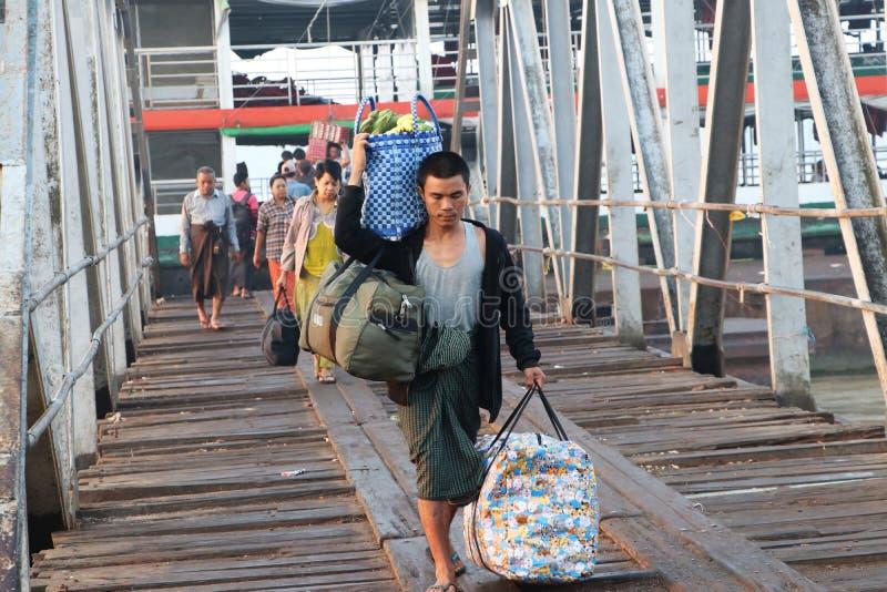 Το άτομο Myanmese που φέρνει τη μεγάλη τσάντα δύο και επωμίζεται το καλάθι της μπανάνας αποβιβάζει από το σκάφος με τον περίπατο  στοκ φωτογραφίες με δικαίωμα ελεύθερης χρήσης