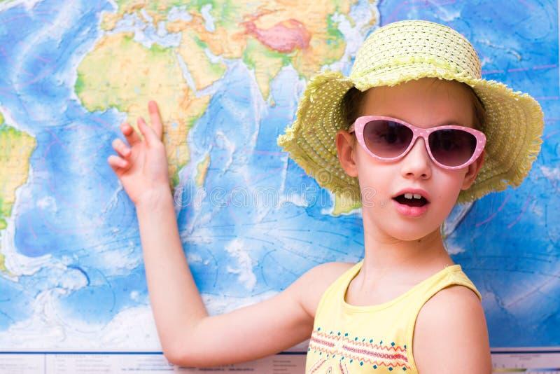 Το έκπληκτο κορίτσι σε ένα καπέλο και τα γυαλιά ηλίου παρουσιάζει σε έναν παγκόσμιο χάρτη στοκ εικόνες