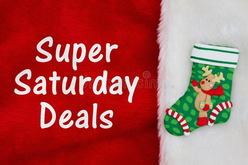Το έξοχο Σάββατο εξετάζει τη γυναικεία κάλτσα Χριστουγέννων με έναν τάρανδο στο κόκκινο και άσπρο κατασκευασμένο ύφασμα βελούδου στοκ φωτογραφία