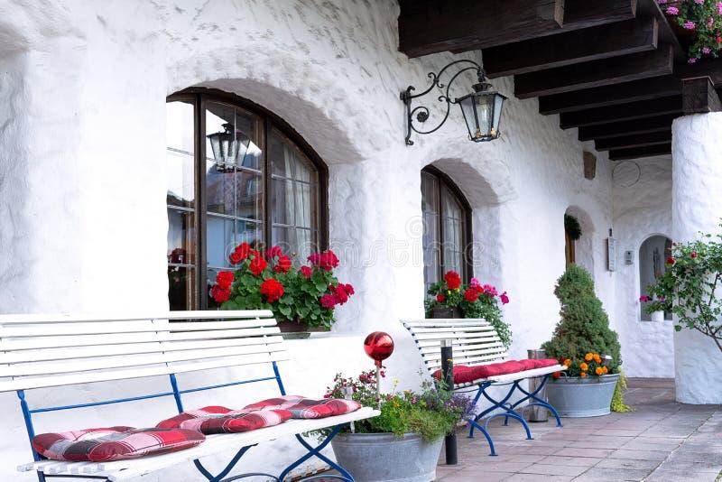 Το έδαφος σπιτιών είναι διακοσμημένο με τα άσπρα καταστήματα, τα λουλούδια και τα σφυρηλατημένα φανάρια στοκ εικόνα