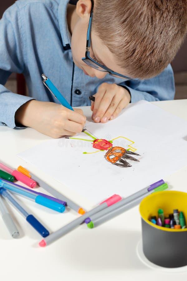 Το αγόρι κάθεται στο γραφείο και επισύρει την προσοχή το φανταστικό αριθμό σε ένα άσπρο κομμάτι χαρτί Οι ζωηρόχρωμοι δείκτες βρίσ στοκ εικόνες