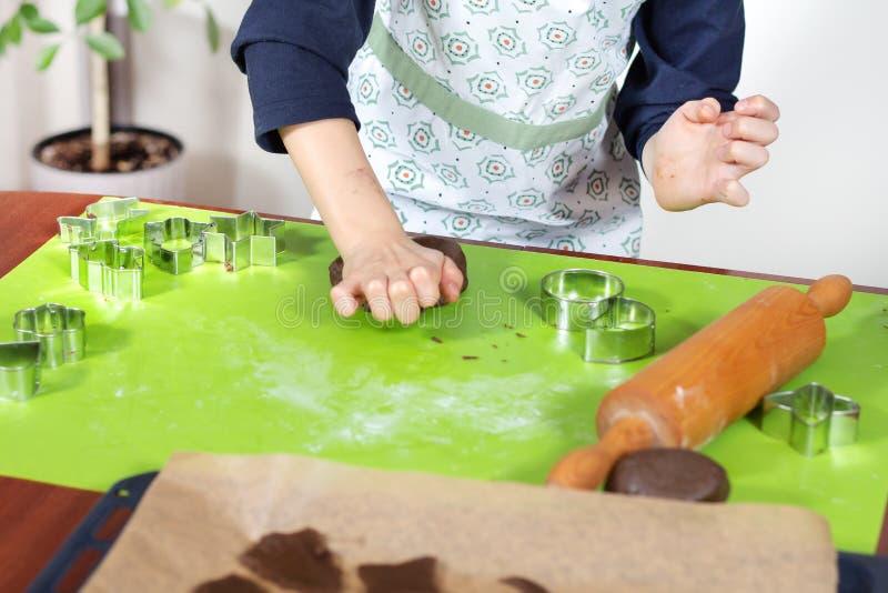 Το αγόρι διαμορφώνει και συντρίβει το καφετί κέικ με το χέρι του Τα έτοιμα μπισκότα και μια ξύλινη κυλώντας καρφίτσα βρίσκονται δ στοκ εικόνα με δικαίωμα ελεύθερης χρήσης