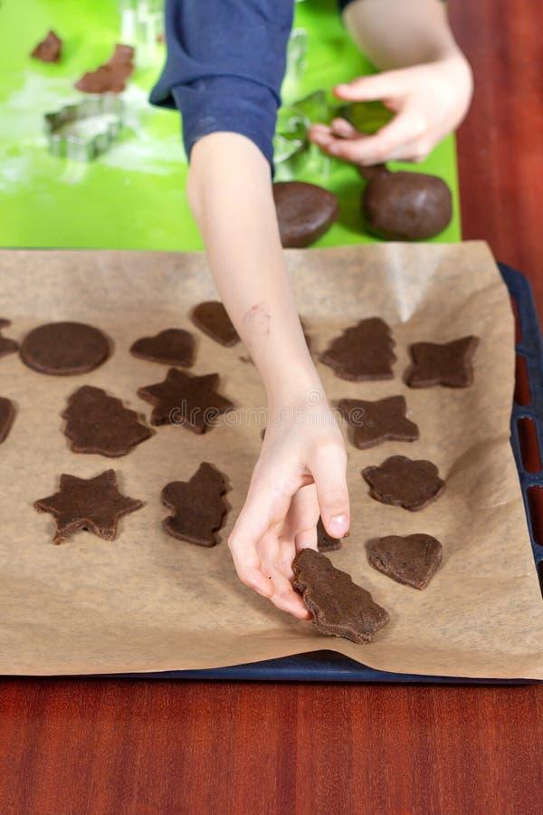 Το αγόρι τακτοποιεί τις αποκόπτως μορφές μπισκότων σε έναν δίσκο ψησίματος Στο υπόβαθρο, κόπτες τραπεζάκι σαλονιού και μπισκότων  στοκ εικόνες