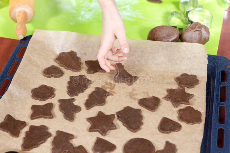 Το αγόρι τακτοποιεί τις αποκόπτως μορφές μπισκότων σε έναν δίσκο ψησίματος Στο υπόβαθρο, κόπτες τραπεζάκι σαλονιού και μπισκότων  στοκ εικόνα με δικαίωμα ελεύθερης χρήσης