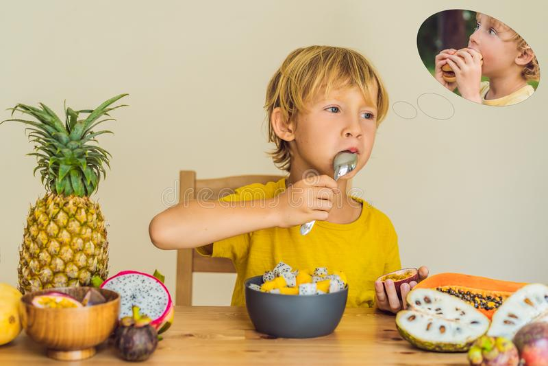 Το αγόρι τρώει τα φρούτα αλλά τα όνειρα για το χάμπουργκερ Επιβλαβή και υγιή τρόφιμα για τα παιδιά Παιδί που τρώει το υγιές πρόχε στοκ εικόνες