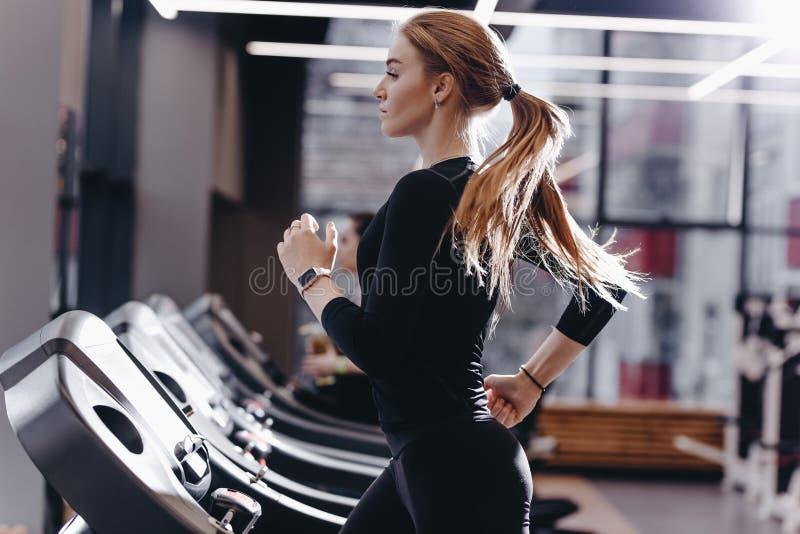 Το αθλητικό κορίτσι έντυσε μαύρο sportswear που τρέχει treadmill στη σύγχρονη γυμναστική στοκ φωτογραφίες