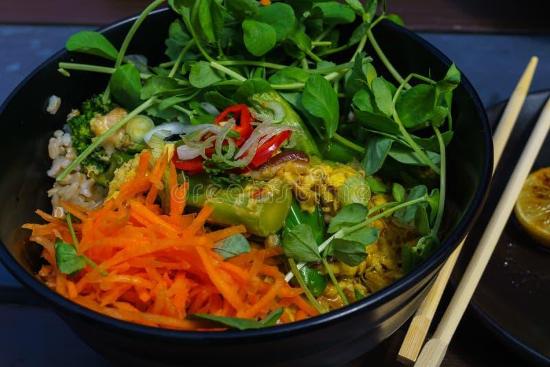 Το ασιατικό τηγανισμένο ρύζι με το αυγό και το λαχανικό και seefoodsand τα βλαστημένα μπιζέλια, στο πιάτο blak εξυπηρετούν με το  στοκ εικόνα με δικαίωμα ελεύθερης χρήσης