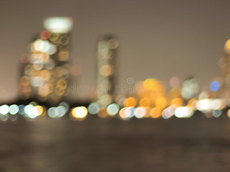 Το αφηρημένο αστικό φως νύχτας bokeh το υπόβαθρο και ο ψαράς στον ποταμό ChaoPhraya Θολωμένο λυκόφως ελαφρύ κτίριο γραφείων με στοκ φωτογραφίες