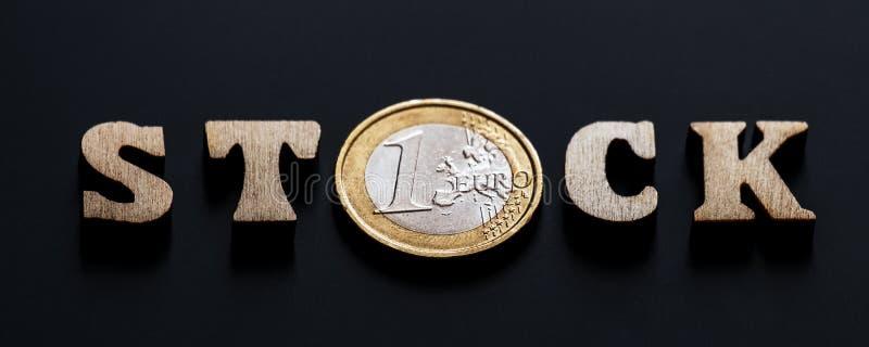Το ΑΠΟΘΕΜΑ λέξης των ξύλινων επιστολών με ένα νόμισμα ενός ευρώ αντί του γράμματος Ο Μαύρο της υφής υπόβαθρο Ρηχό βάθος στοκ φωτογραφία