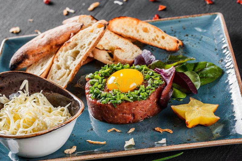Το βόειο κρέας tartare εξυπηρέτησε με έναν λέκιθο αυγών, τεμαχισμένα πράσινα κρεμμύδια, μια φρυγανιά και ένα βούτυρο στο πιάτο στ στοκ εικόνες