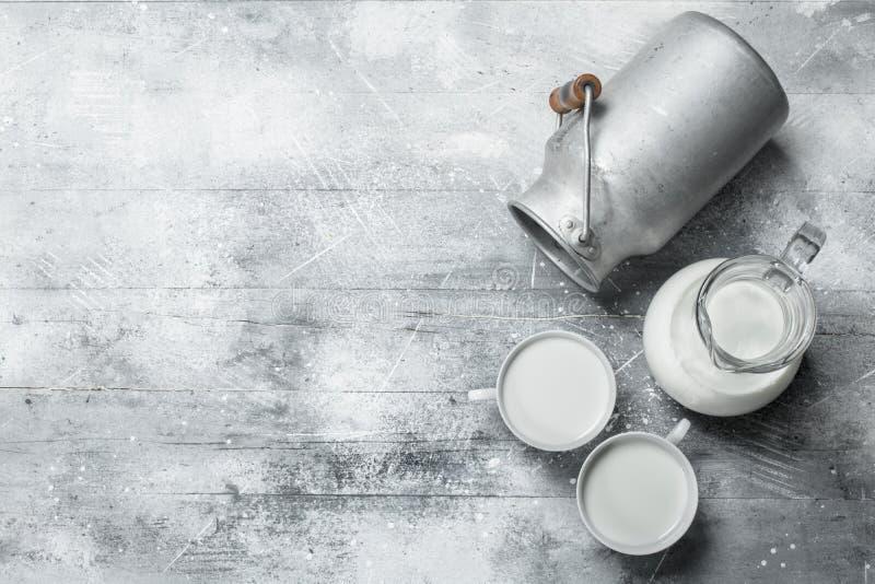Το γάλα στις κούπες με το α μπορεί στοκ εικόνες