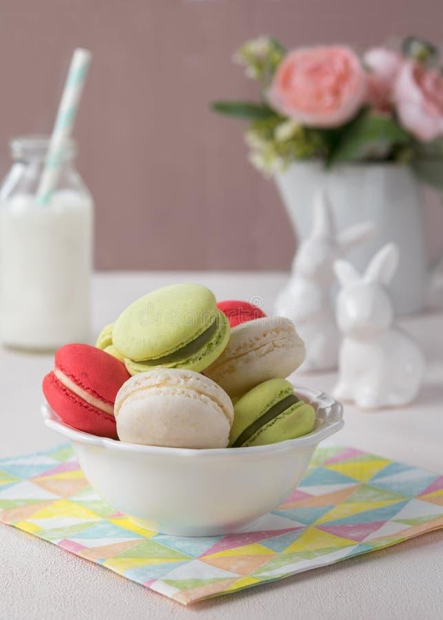 Το γαλλικό μπισκότο Macaron ή macaroon στο ελαφρύ υπόβαθρο με την άνοιξη ανθίζει, χρώματα κρητιδογραφιών με το διάστημα αντιγράφω στοκ φωτογραφία με δικαίωμα ελεύθερης χρήσης