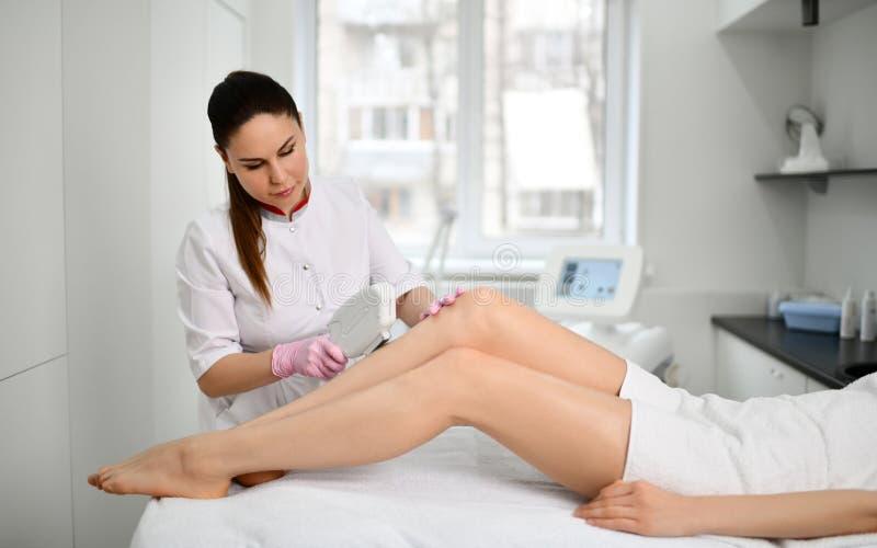 Το γιατρός-Cosmetician εκτελεί μια καλλυντική διαδικασία στα πόδια του ασθενή με την ηλεκτρονική ιατρική συσκευή στο ινστιτούτο κ στοκ φωτογραφία