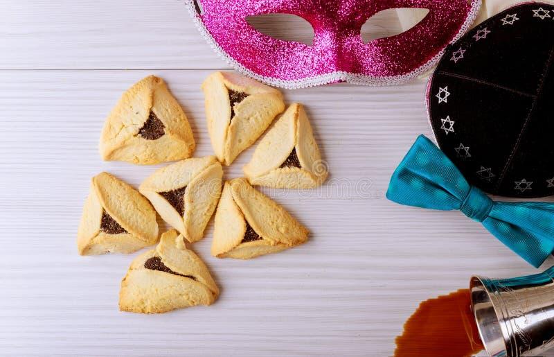 Το εβραϊκό purim τα σπιτικά μπισκότα με τη μάσκα purim και purim kippah το κόκκινο kosher κρασί στοκ εικόνες