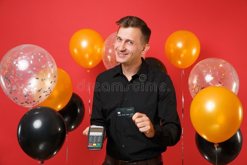 Το ελκυστικό άτομο που κρατά το ασύρματο σύγχρονο τερματικό πληρωμής τραπεζών στη διαδικασία, αποκτά τις πληρωμές με πιστωτική κά στοκ φωτογραφία με δικαίωμα ελεύθερης χρήσης