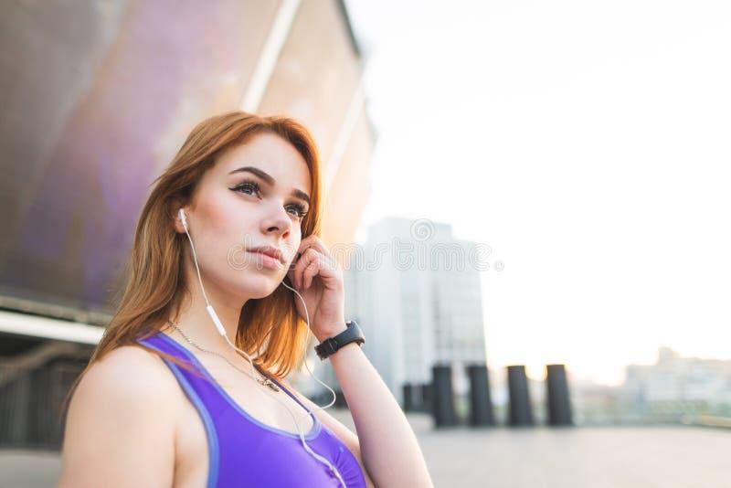 Το ελκυστικό αθλητικό κορίτσι ακούει τη μουσική στα ακουστικά jogging, κοιτάζει κατά μέρος, στέκεται στοκ εικόνες με δικαίωμα ελεύθερης χρήσης