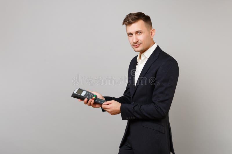Το ελκυστικό επιχειρησιακό άτομο που κρατά το ασύρματο σύγχρονο τερματικό πληρωμής τραπεζών στη διαδικασία, αποκτά τις πληρωμές μ στοκ εικόνα