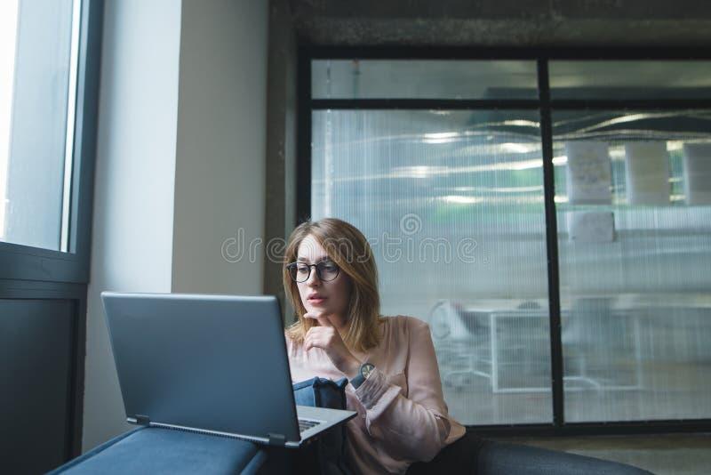 Το ελκυστικό κορίτσι εξετάζει το σημειωματάριο στο υπόβαθρο του χώρου γραφείου Το κορίτσι εργάζεται σε ένα lap-top σε έναν καναπέ στοκ εικόνες