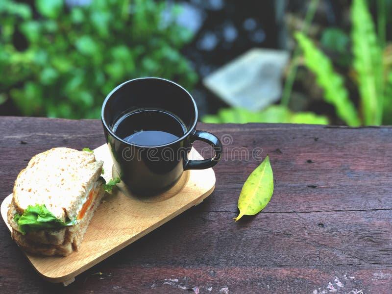 Το εύγευστο πρόγευμα τοπ άποψης με το φρέσκο σάντουιτς και ο μαύρος καφές κοιλαίνουν στον ξύλινο πίνακα στοκ φωτογραφία