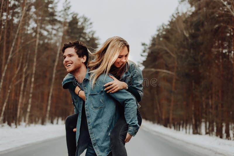 Το ευτυχές εύθυμο χαμογελώντας ζεύγος των νέων στο τζιν ταιριάζει στο χιονώδες δάσος το χειμώνα στο δρόμο τοποθετήστε το κείμενο στοκ εικόνα με δικαίωμα ελεύθερης χρήσης