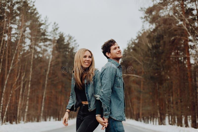 Το ευτυχές εύθυμο χαμογελώντας ζεύγος των νέων στο τζιν ταιριάζει στο χιονώδες δάσος το χειμώνα στο δρόμο τοποθετήστε το κείμενο στοκ εικόνα