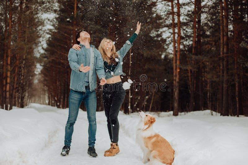 Το ευτυχές εύθυμο χαμογελώντας ζεύγος των νέων στο τζιν ταιριάζει στο χιονώδες δάσος το χειμώνα με το κόκκινο κόλλεϊ συνόρων σκυλ στοκ φωτογραφίες