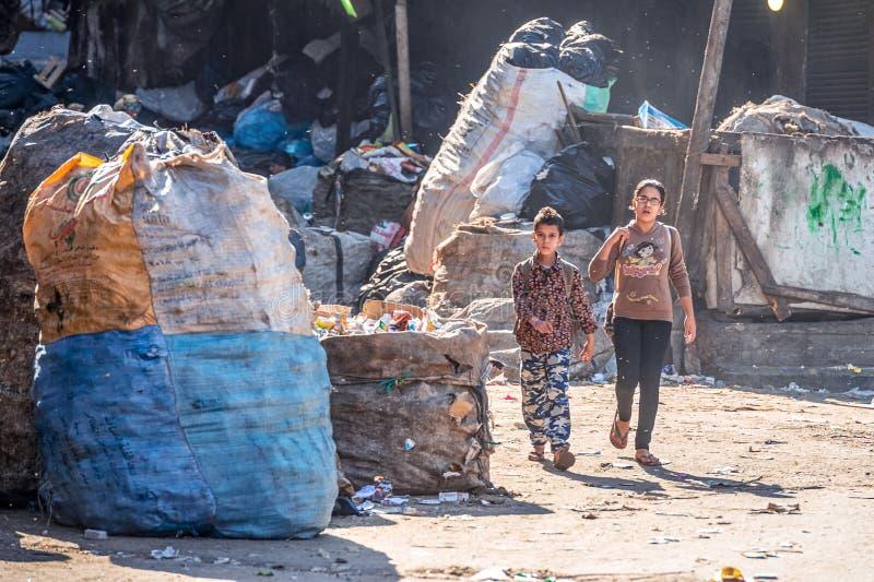 11/18/2018 το Κάιρο, Αίγυπτος, παιδιά πηγαίνει στο σχολείο στην οδό μιας πόλης απορριμάτων μεταξύ μιας δέσμης των απορριμάτων στοκ εικόνες με δικαίωμα ελεύθερης χρήσης