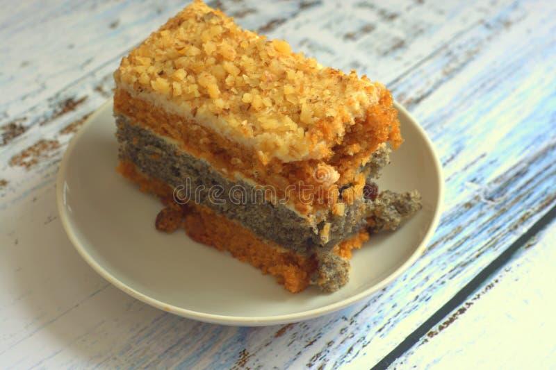Το κέικ σφουγγαριών με τους σπόρους παπαρουνών σε ένα πιάτο βρίσκεται σε έναν ξύλινο πίνακα στοκ φωτογραφία