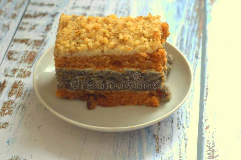 Το κέικ σφουγγαριών με τους σπόρους παπαρουνών σε ένα πιάτο βρίσκεται σε έναν ξύλινο πίνακα στοκ φωτογραφίες με δικαίωμα ελεύθερης χρήσης
