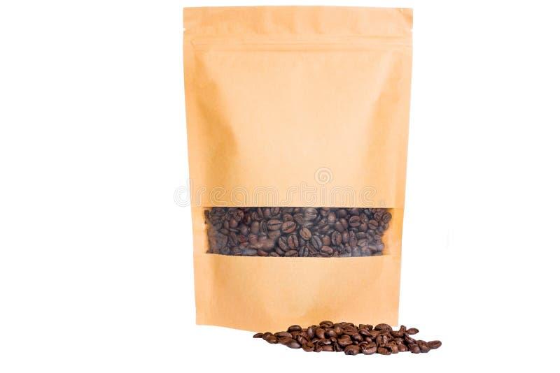 Το καφετί έγγραφο doypack στέκεται επάνω τη σακούλα με το φερμουάρ παραθύρων που γεμίζουν με τα φασόλια καφέ στο άσπρο υπόβαθρο στοκ φωτογραφία με δικαίωμα ελεύθερης χρήσης