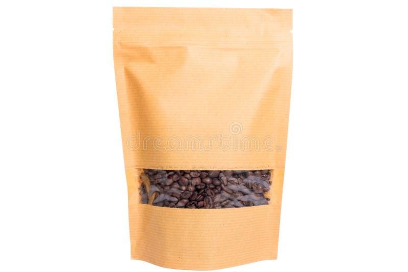 Το καφετί έγγραφο doypack στέκεται επάνω τη σακούλα με το φερμουάρ παραθύρων που γεμίζουν με τα φασόλια καφέ στο άσπρο υπόβαθρο στοκ εικόνες με δικαίωμα ελεύθερης χρήσης
