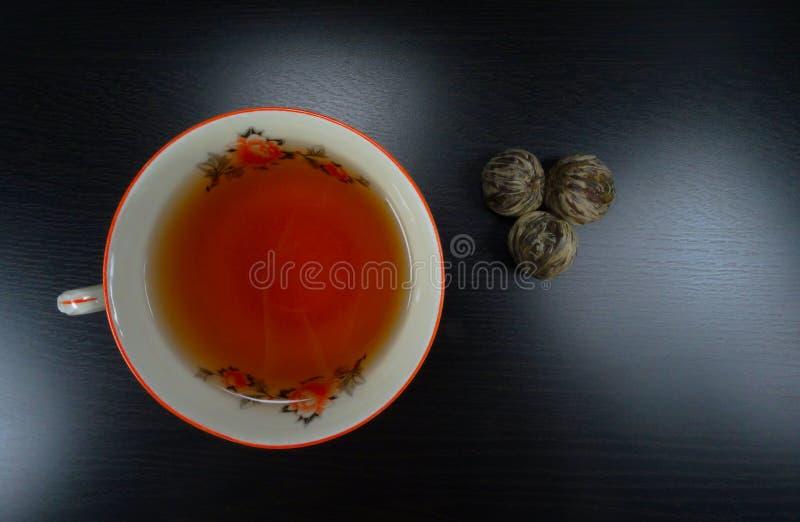 Το καυτό φλυτζάνι τσαγιού porselain με το τσάι ανθίζει σε ένα μαύρο ξύλινο υπόβαθρο teatime! στοκ εικόνα