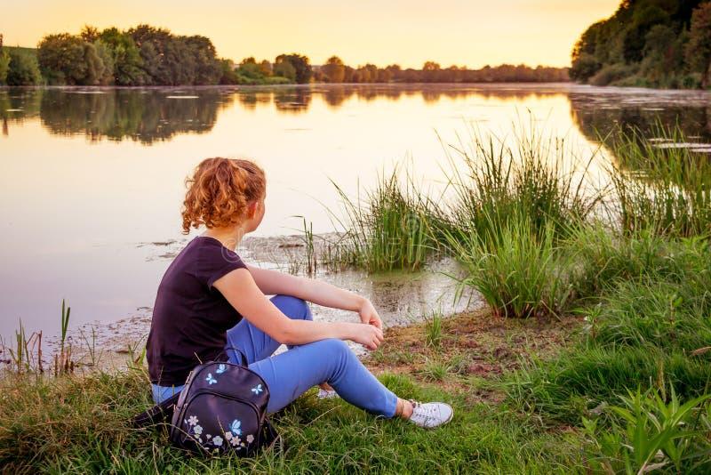 Το κορίτσι κάθεται από τον ποταμό και απολαμβάνει το βράδυ calm_ στοκ φωτογραφίες