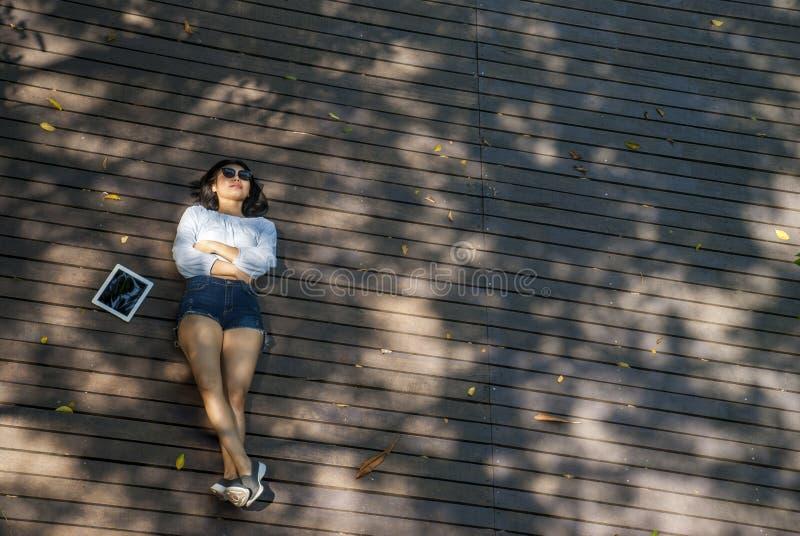 Το κορίτσι κάθισε στην ταμπλέτα καθμένος στον κήπο στοκ εικόνες
