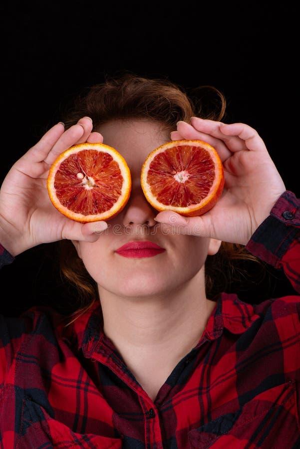 Το κορίτσι με το κόκκινο κραγιόν στα χείλια της κρατά μπροστά από τα μάτια της τα κομμάτια του κόκκινου πορτοκαλιού Έννοια Makeup στοκ φωτογραφία