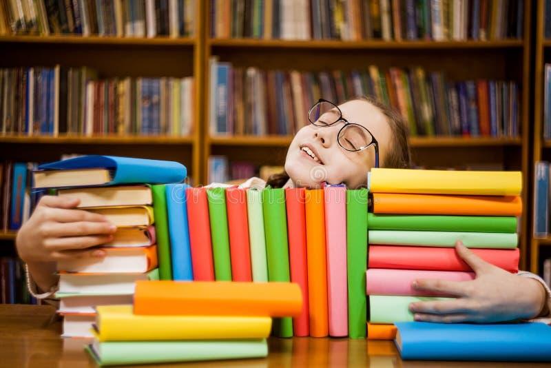 Το κορίτσι στα γυαλιά στη βιβλιοθήκη αγκαλιάζει τα βιβλία στοκ εικόνες