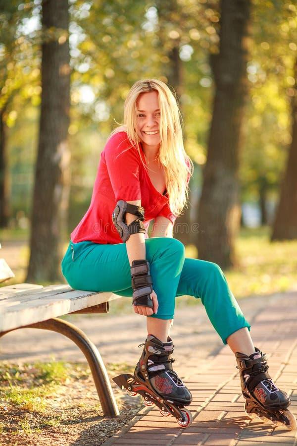 Το κορίτσι στους κυλίνδρους έχει τη διασκέδαση στο θερινό πάρκο πόλεων, απολαμβάνοντας υγιή lifestile στοκ φωτογραφία με δικαίωμα ελεύθερης χρήσης