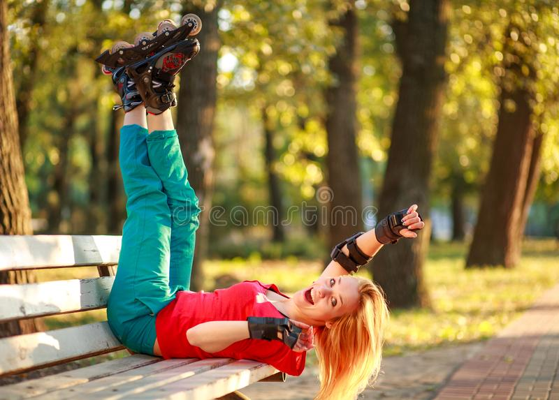 Το κορίτσι στους κυλίνδρους έχει τη διασκέδαση στο θερινό πάρκο πόλεων, απολαμβάνοντας υγιή lifestile στοκ εικόνες