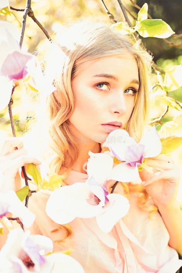 Το κορίτσι στο ονειροπόλο πρόσωπο, υποβάλλει προσφορά τα ξανθά κοντινά λουλούδια magnolia, υπόβαθρο φύσης Η νέα γυναίκα απολαμβάν στοκ φωτογραφίες