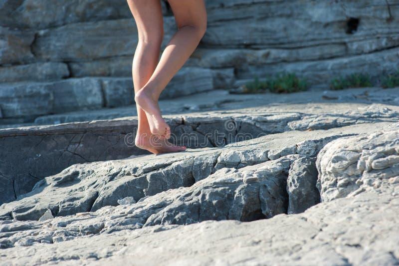 Το κορίτσι πηγαίνει χωρίς παπούτσια στους βράχους, αναρριμένος επάνω στοκ φωτογραφίες