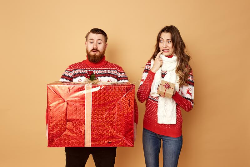 Το κορίτσι που κρατά ένα μικρό δώρο εξετάζει surprisely τον τύπο κρατώντας ένα τεράστιο δώρο Και οι δύο είναι ντυμένοι κόκκινος κ στοκ φωτογραφία