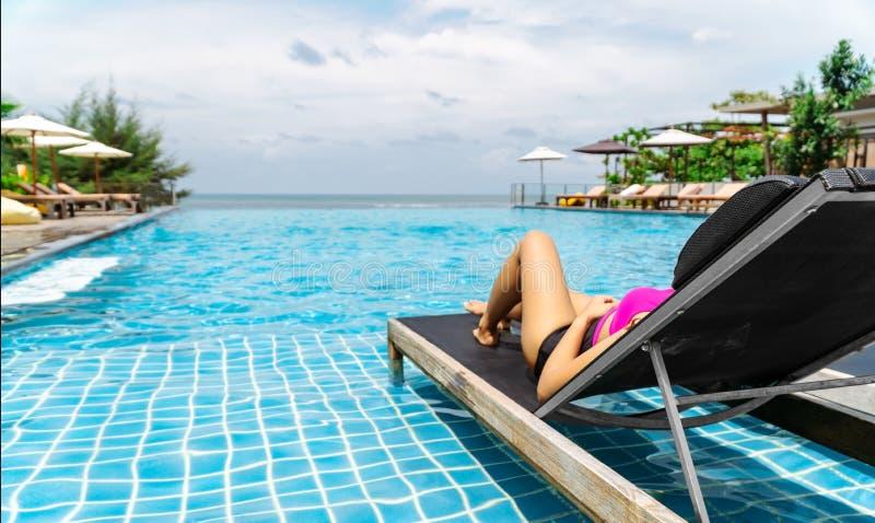 Το κορίτσι που φορά το μπικίνι ή swimwear κάνει ηλιοθεραπεία από τη λίμνη στοκ φωτογραφία